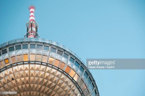low angle view of modern building against blue sky - television tower berlin stock pictures, royalty-free photos & images