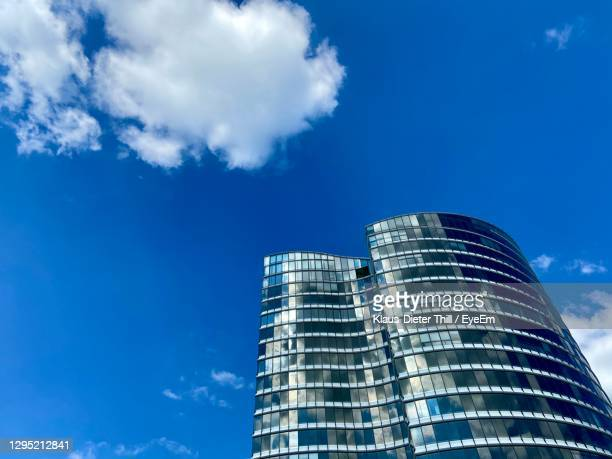low angle view of modern building against blue sky - klaus-dieter thill stock-fotos und bilder