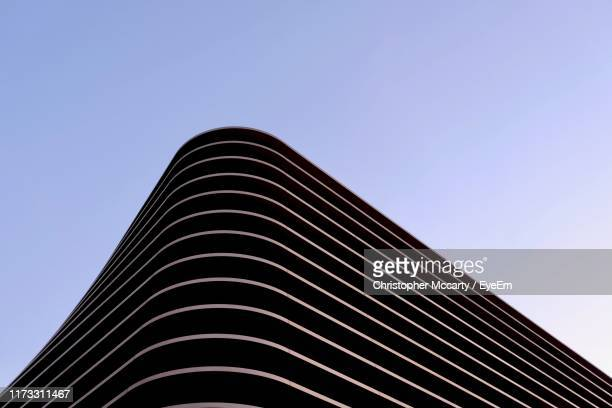 low angle view of modern building against clear blue sky - arquitectura fotografías e imágenes de stock