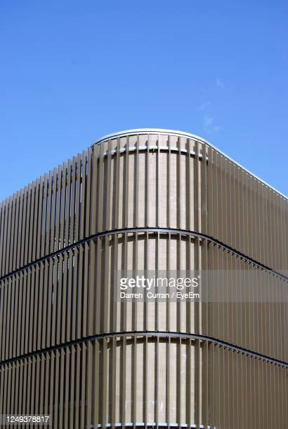 low angle view of modern building against clear blue sky - curran stock pictures, royalty-free photos & images