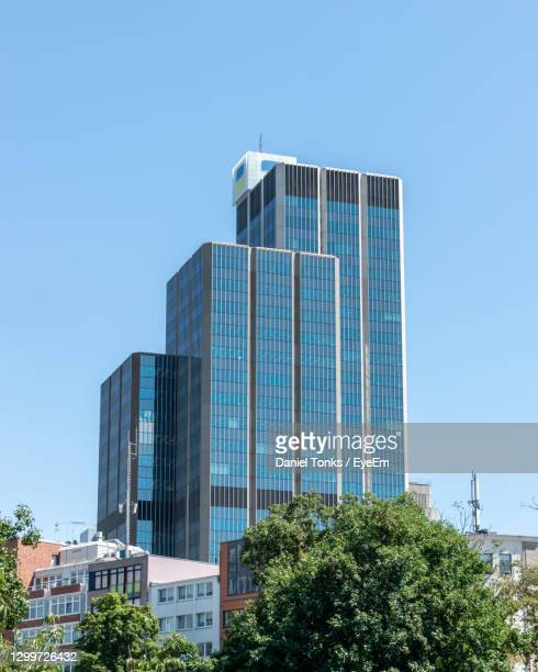 low angle view of modern building against clear blue sky - headquarters stock-fotos und bilder