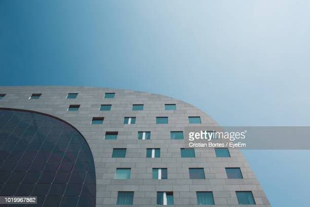 low angle view of modern building against clear sky - rotterdam stock pictures, royalty-free photos & images
