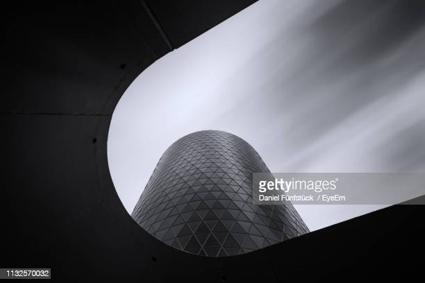 low angle view of modern building against cloudy sky - frankfurt main tower stock pictures, royalty-free photos & images