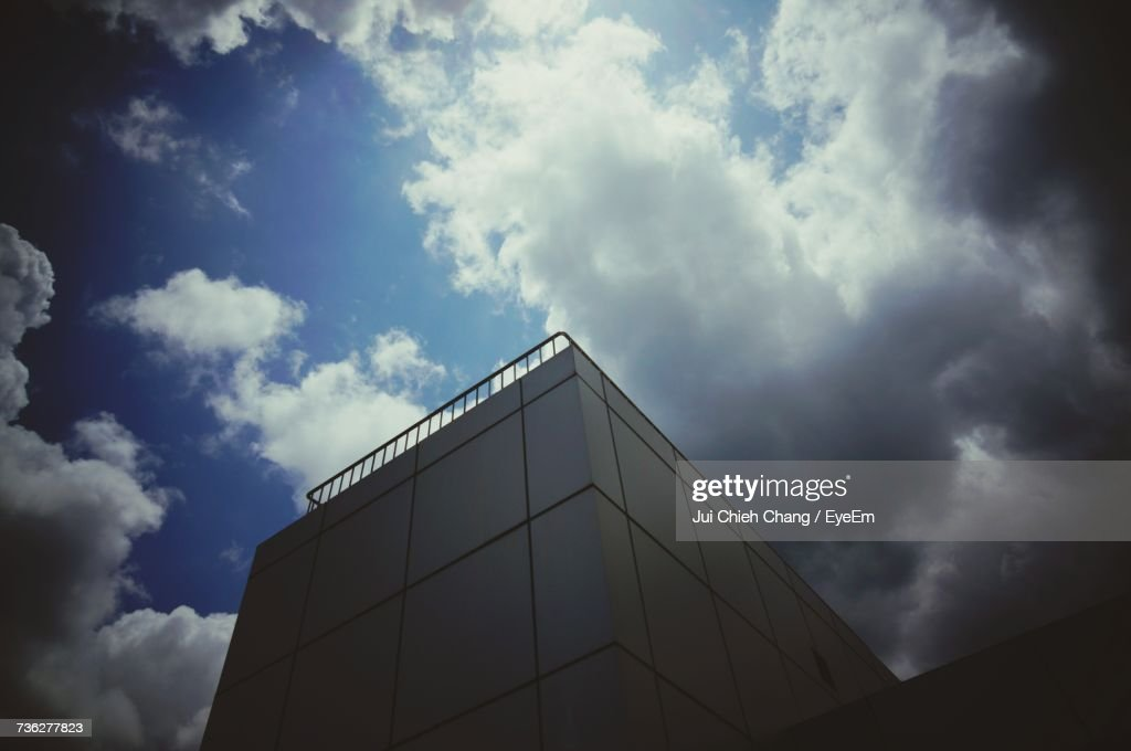 Low Angle View Of Modern Building Against Cloudy Sky : Stock Photo