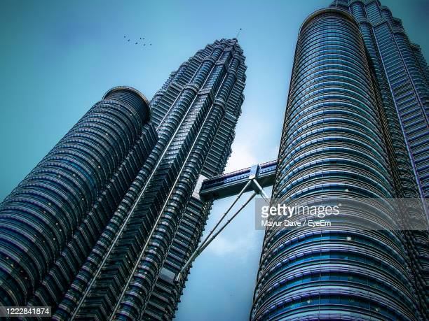 low angle view of modern building against sky - petronas towers stock pictures, royalty-free photos & images