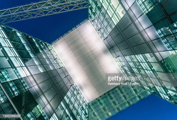 low angle view of modern buildings against blue sky - headquarters stock pictures, royalty-free photos & images