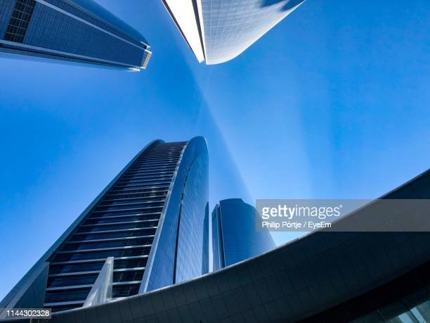 low angle view of modern buildings against clear blue sky - abu dhabi stock pictures, royalty-free photos & images