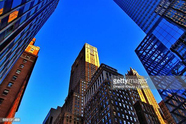 low angle view of modern buildings against clear blue sky - krausz stock-fotos und bilder