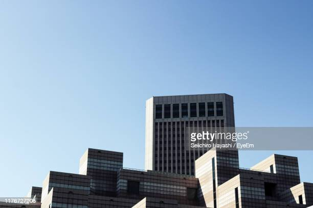 low angle view of modern buildings against clear sky - seiichiro hayashi ストックフォトと画像