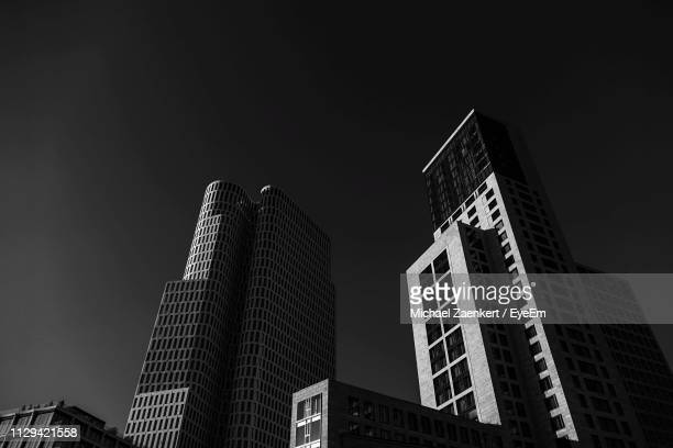 low angle view of modern buildings against sky at night - kapitalismus stock-fotos und bilder