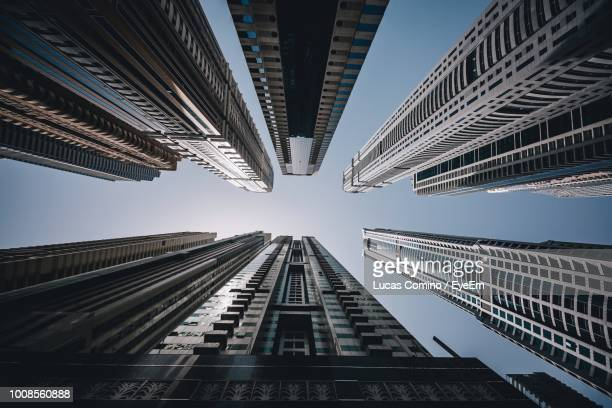low angle view of modern buildings against sky in city - wolkenkrabber stockfoto's en -beelden