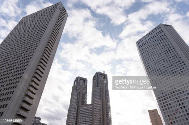 low angle view of modern buildings against sky in city - 真下からの眺め ストックフォトと画像
