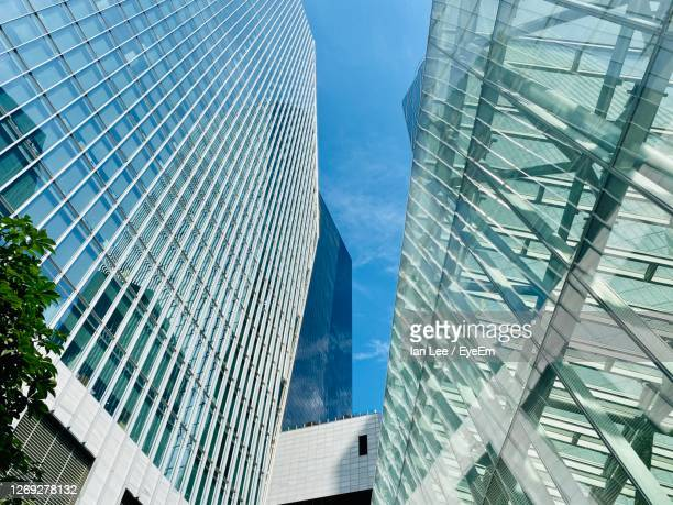 low angle view of modern buildings against sky - headquarters stock pictures, royalty-free photos & images