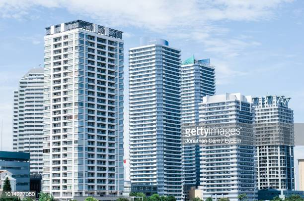 low angle view of modern buildings in city against sky - 外壁 ストックフォトと画像