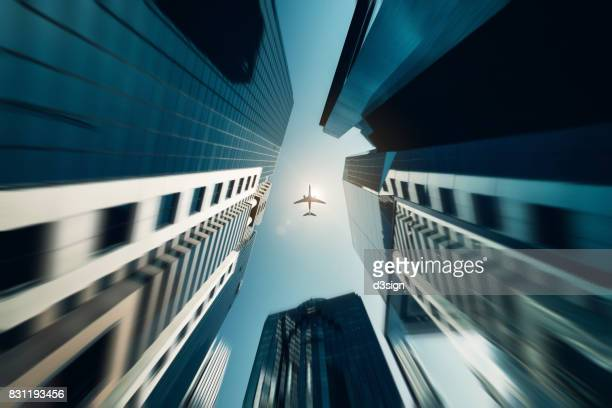 Low angle view of modern business towers with airplane flying over