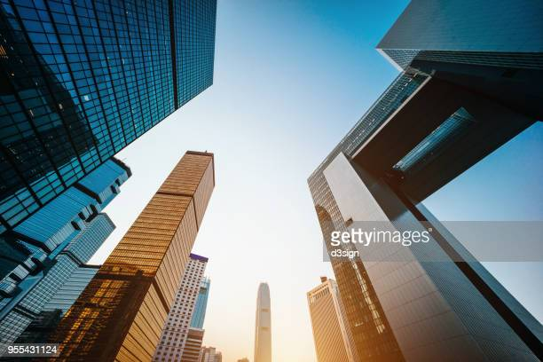 low angle view of modern financial skyscrapers in central business district, hong kong at sunrise - bank financial building stock pictures, royalty-free photos & images