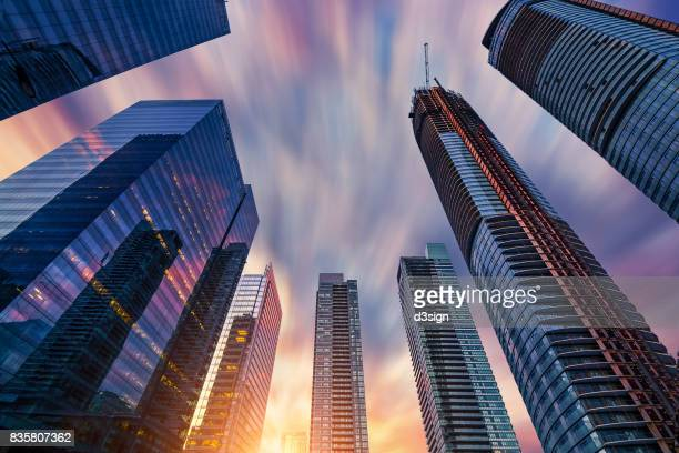 Low angle view of modern financial skyscrapers rising straight up against dramatic sky in downtown Toronto