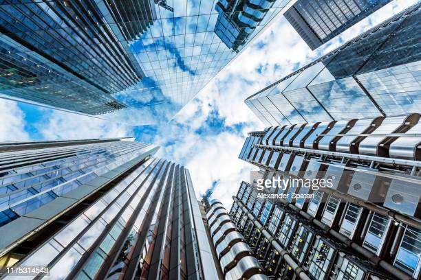 low angle view of modern futuristic skyscrapers in the city of london, england, uk - skyscraper stock pictures, royalty-free photos & images