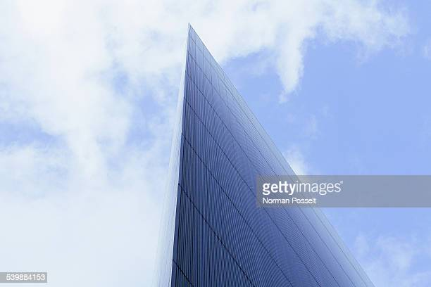 low angle view of modern glass building against cloudy sky - skyscraper stock pictures, royalty-free photos & images