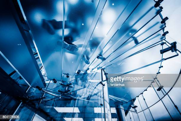 low angle view of modern glass spiral staircase in business office