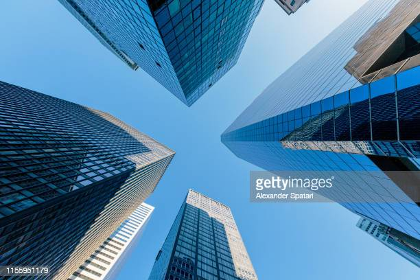 low angle view of modern skyscrapers against clear blue sky in manhattan downtown, new york - skyscraper stock pictures, royalty-free photos & images