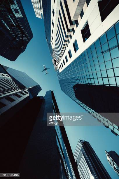 Low angle view of modern skyscrapers in Hong Kong downtown with airplane flying above