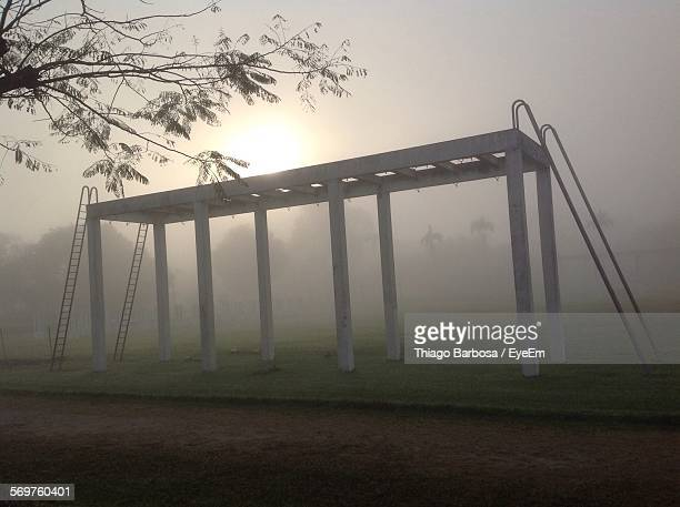 Low Angle View Of Monkey Bars On Grassy Field During Foggy Weather
