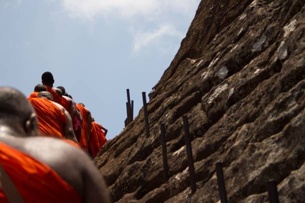 Low Angle View Of Monks Climbing On Rock Formation Against Sky
