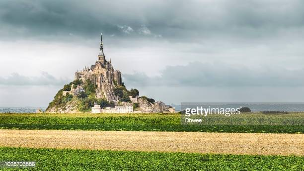 low angle view of mont saint michel in a cloudy day - camino de santiago stock pictures, royalty-free photos & images