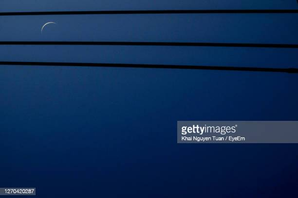 low angle view of moon against blue sky - blue angels stock pictures, royalty-free photos & images