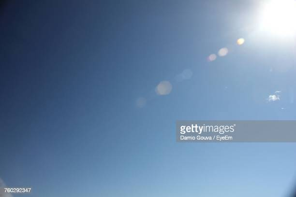 low angle view of moon against blue sky - lens flare stock pictures, royalty-free photos & images