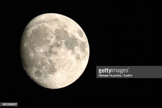 low angle view of moon against clear sky at night - michael hruschka stock-fotos und bilder