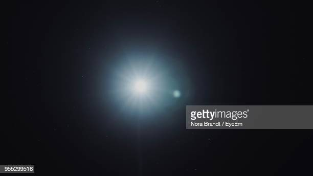 low angle view of moon against sky at night - lens flare stock pictures, royalty-free photos & images