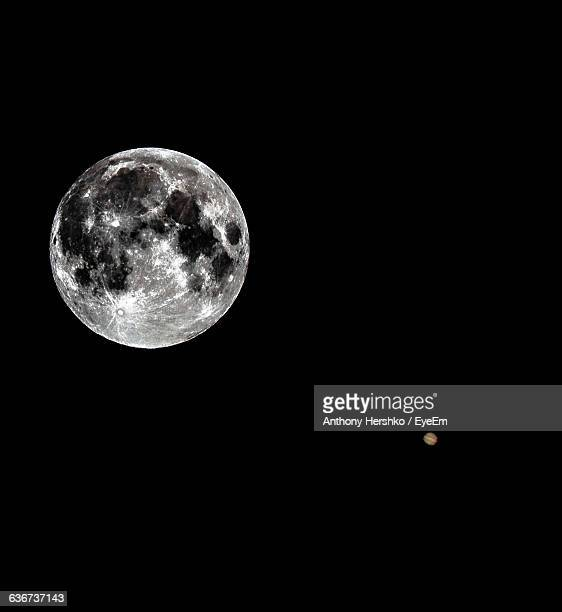 Low Angle View Of Moon And Planet Jupiter Against Clear Sky