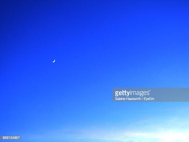 Low Angle View Of Moon At Blue Sky