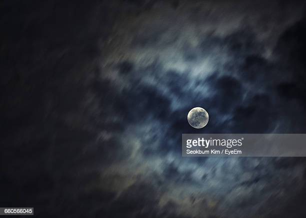 Low Angle View Of Moon At Cloudy Sky