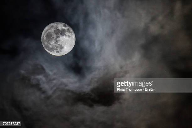 low angle view of moon in cloudy sky - luna nera foto e immagini stock