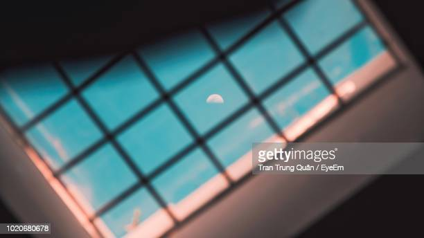 low angle view of moon in sky seen through window ceiling - photographed through window stock pictures, royalty-free photos & images