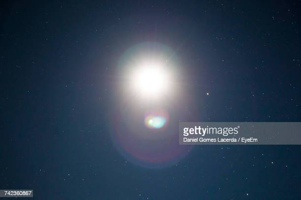 low angle view of moon with lens flare against star field at night - blendenfleck stock-fotos und bilder