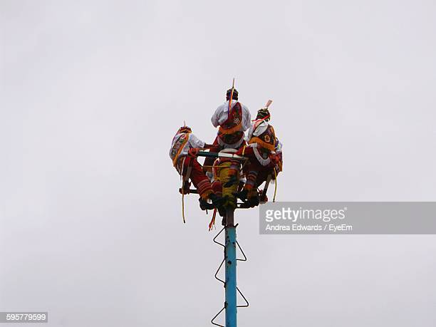Low Angle View Of Morris Dancers Performing On Pole Against Sky