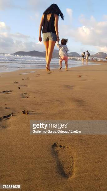 Low Angle View Of Mother With Daughter Walking At Beach