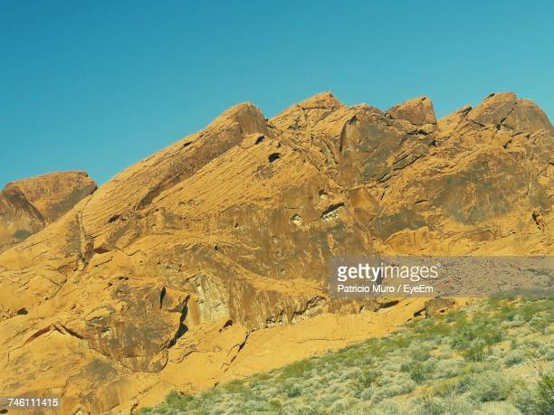 low angle view of mountain against clear blue sky - muro stock photos and pictures