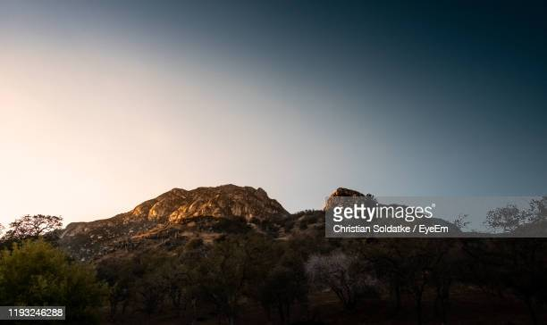 low angle view of mountain against clear sky - christian soldatke foto e immagini stock