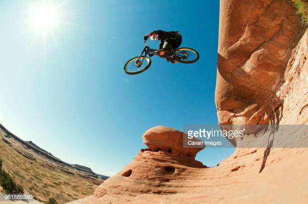 low angle view of mountain biker jumping from cliff against clear blue sky - weitwinkel stock-fotos und bilder