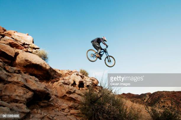Low angle view of mountain biker performing stunt in mid-air