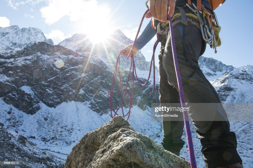 Low angle view of mountain climber with rope in mountains : Stock Photo