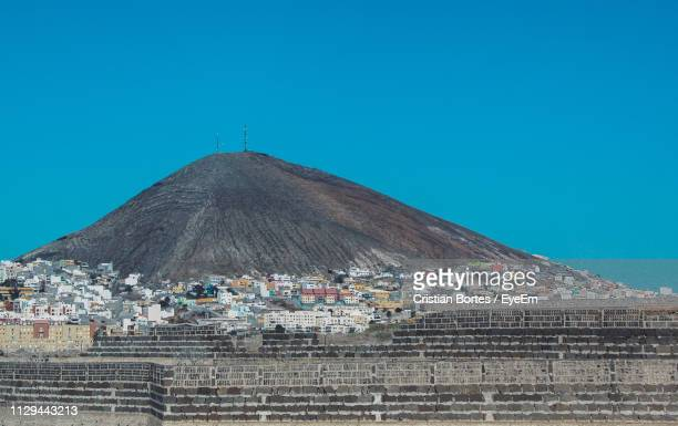Low Angle View Of Mountain In City Against Clear Blue Sky