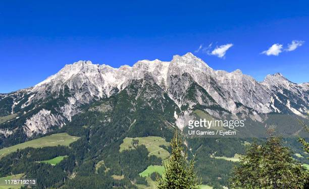 low angle view of mountain range against blue sky - leogang stock pictures, royalty-free photos & images