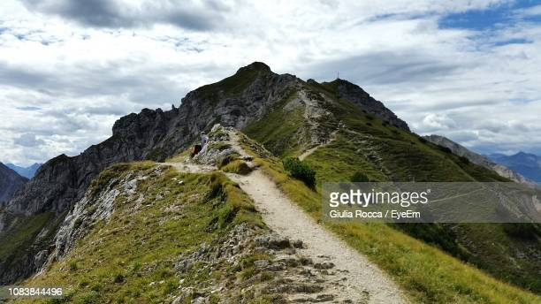 low angle view of mountain range against sky - uphill stock pictures, royalty-free photos & images