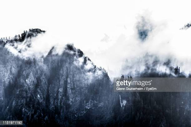 low angle view of mountains against cloudy sky - stutterheim stock photos and pictures